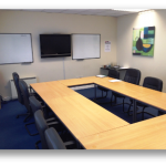 meeting room with large joined table, television display and whiteboards